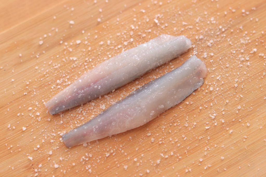 メヒカリに塩をふる
