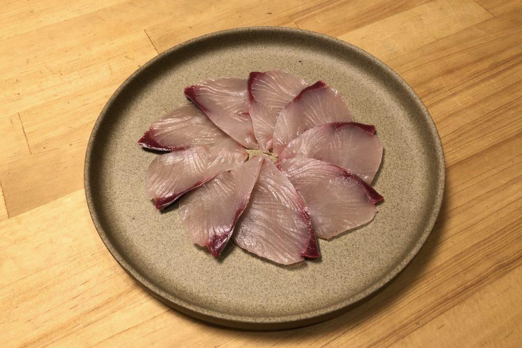 薄く切ったブリをお皿に並べる